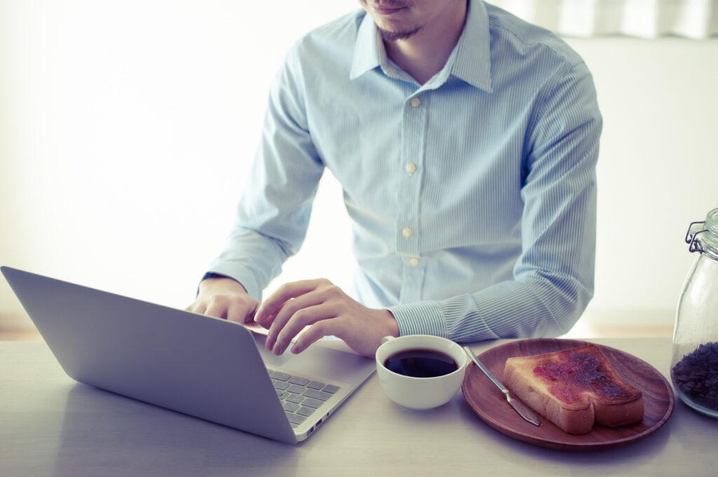 朝食を食べながらノートパソコンを操作している笑顔の男性